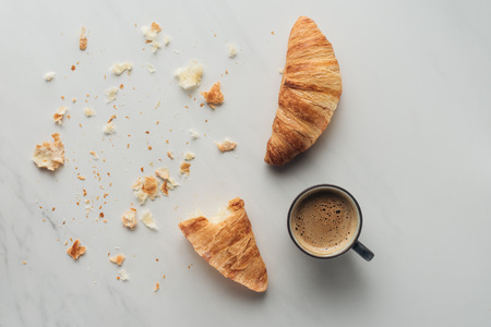 top view of coffee cup and croissants on white marble
