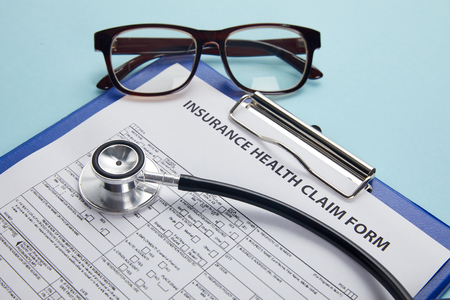 insurance health claim form, clipboard, eyeglasses and stethoscope on blue 版權商用圖片