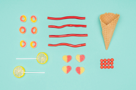 flat lay of jelly candies, dragee, lollipops and waffle cone isolated on turquoise Stock Photo