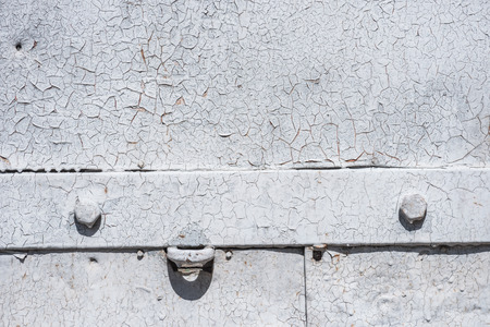 detail of old metal gate with scratched weathered white paint