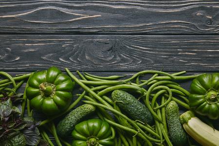 Green summer vegetables on dark wooden table