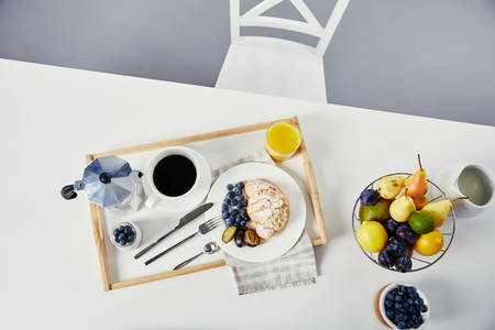 top view of croissant with fresh blueberries and plum pieces, glass of juice, cup of coffee and yogurt for breakfast on wooden tray on white tabletop Фото со стока
