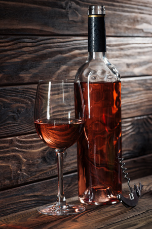 wine bottle, glass of wine and corkscrew on wooden table