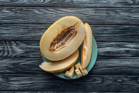 top view of sweet ripe sliced melon on plate on wooden surface Stock Photo