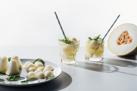 close-up view of sweet melon balls and refreshing beverage with melon and mint in glasses on white