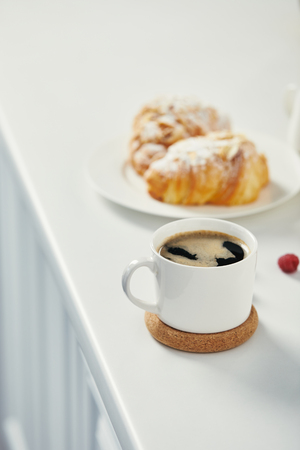 close up view of cup of aromatic coffee and croissants for breakfast on white surface Stockfoto