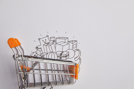 top view of shopping cart with little goods made of paper on grey background 写真素材