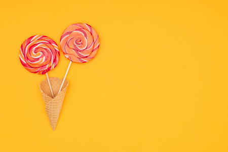 top view of yummy round lollipops in waffle cone isolated on orange
