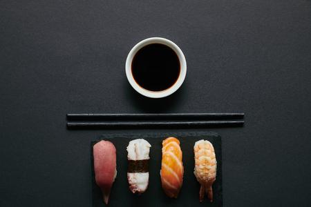top view of assorted nigiri sushi set, chopsticks and soya sauce on black slate plate on dark tabletop