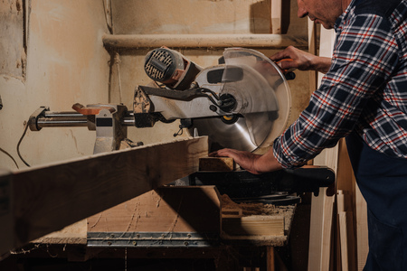 partial view of carpenter using saw at wooden workshop Zdjęcie Seryjne
