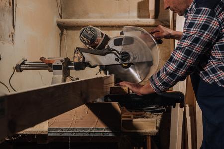 Vue partielle du menuisier à l'aide d'une scie à l'atelier en bois Banque d'images