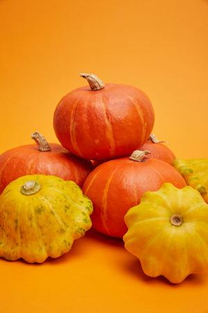 close-up view of pile of fresh raw ripe pumpkins on orange