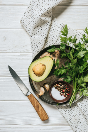 top view of ripe avocado, parsley and bowl with pepper on white wooden table