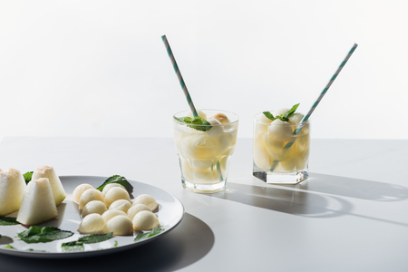 sweet melon balls and refreshing beverage with melon and mint in glasses on white