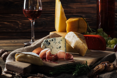 different types of cheeses and prosciutto on wooden board