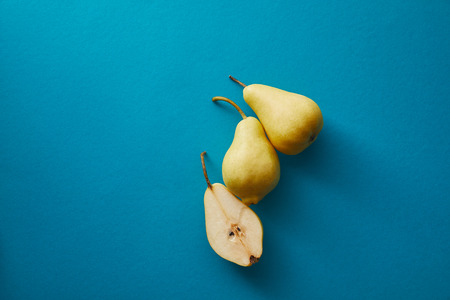 top view of ripe pears on blue surface