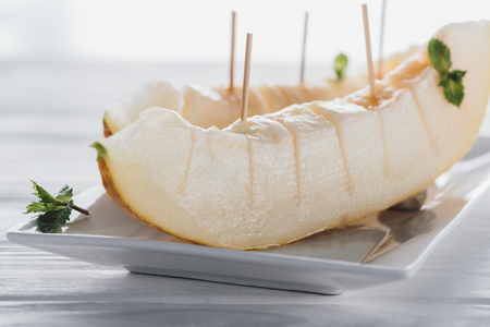close-up view of sliced sweet ripe melon with mint on plate Stock Photo