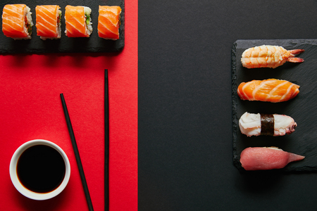 flat lay with soya sauce in bowl, chopsticks and sushi sets on black slate plates on red and black background Banque d'images