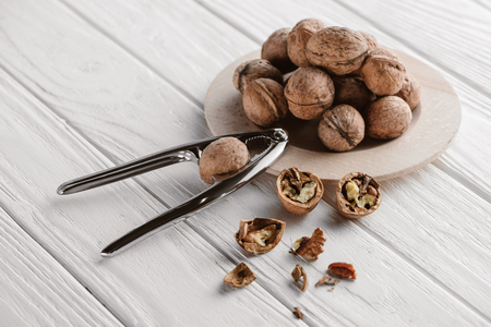 walnuts with metal nutcracker on wooden background