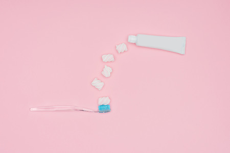 top view of marshmallows, toothbrush and toothpaste tube isolated on pink