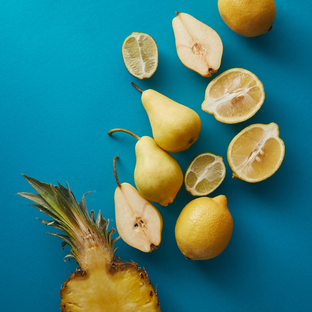 top view of ripe pineapple, pears and lemons on blue surface