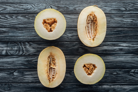 top view of halved ripe sweet honeydew and cantaloupe melons on wooden surface