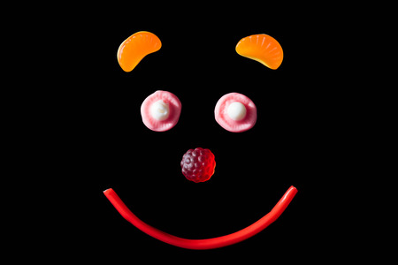 top view of smiley of jelly candies isolated on black Stock Photo