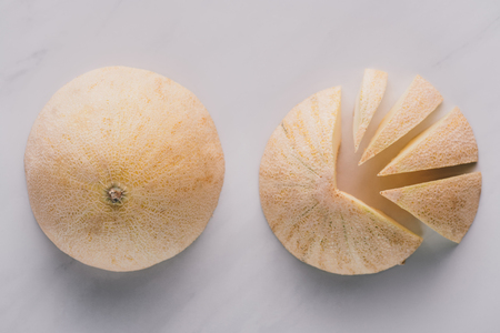 top view of whole and sliced honeydew melons on white