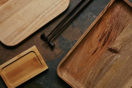 flat lay with empty wooden plates and chopsticks for sushi on dark tabletop Stockfoto