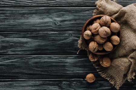 brown walnuts in wooden bowl on dark wooden surface