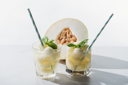 close-up view of summer drink with melon and mint in glasses and half of ripe honeydew melon on white Stock Photo