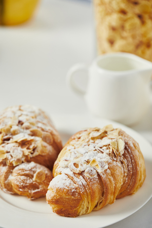 close up view of sweet croissants with sugar powder for breakfast on white tabletop