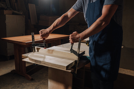 cropped shot of carpenter in apron working on wood at workshop