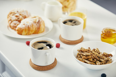 close up view of cups of coffee, croissants and raspberries for breakfast on white surface Stockfoto