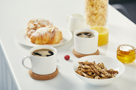 close up view of cups of coffee, honey and croissants for breakfast on white surface
