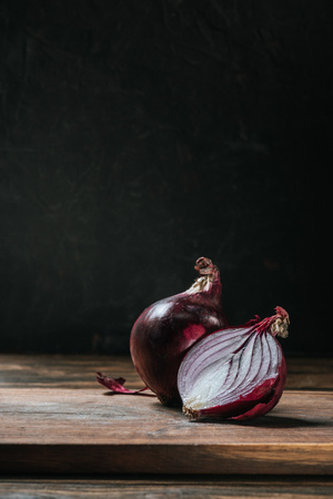 ripe cut red onion on cutting board isolated on black Reklamní fotografie