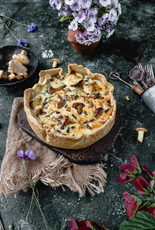 appetizing quiche with mushrooms and potted flowers on wooden table Stock Photo