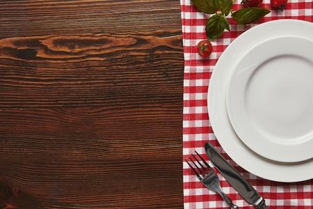 Vista superior de platos blancos vacíos, cubiertos y albahaca fresca con tomates en la superficie de madera