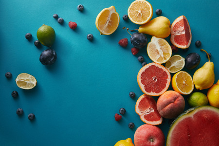 elevated view of appetizing ripe fruits and berries on blue surface