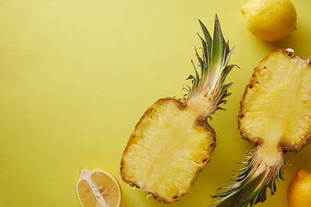top view of pineapple and lemons on yellow surface