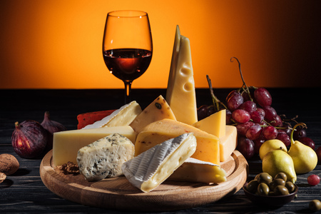 different types of cheeses, glass of wine and fruits on table on orange
