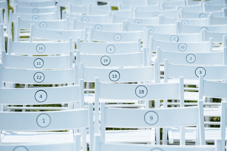 empty white chairs with numbers in rows outdoor Archivio Fotografico - 106890558