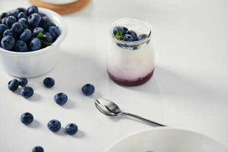 close up view of fresh blueberries and yogurt for breakfast on white tabletop with spoon Stockfoto