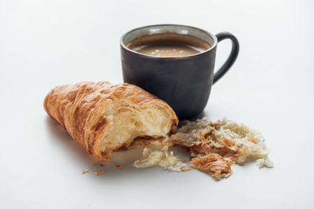 close-up shot of coffee cup and bitten croissant on white 版權商用圖片