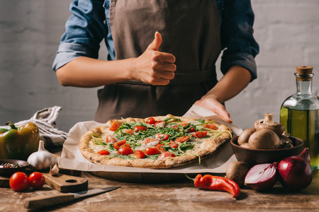 cropped shot of woman in apron showing thumb up at tabletop with italian pizza Фото со стока