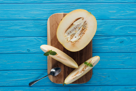 top view of sweet ripe sliced melon with mint and spoon on cutting board on blue wooden surface