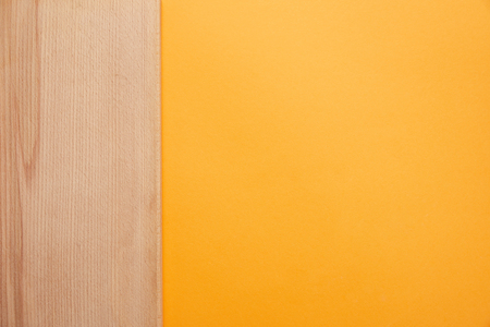 top view of bright orange background and wooden surface