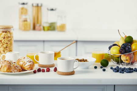 close up view of cups of coffee and croissants for breakfast on white tabletop in kitchen