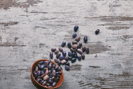 Dry haricot beans in bowl on rustic wooden table