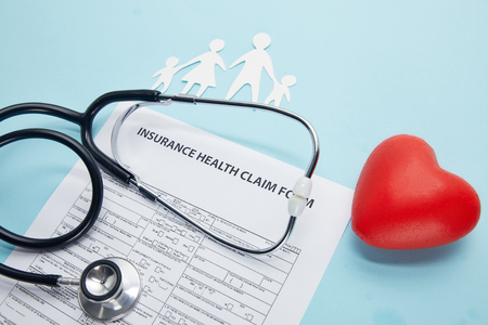 close-up view of insurance health claim form, paper cut family, red heart symbol and stethoscope on blue